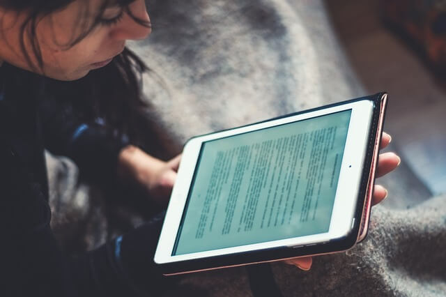 girl reading content writing services in an ipad